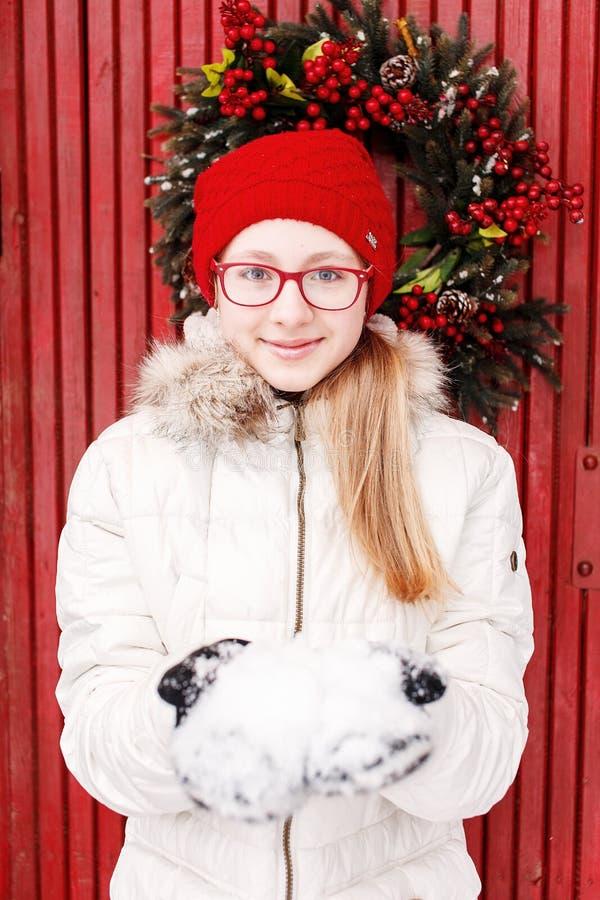 白色拿着雪的外套和红色帽子的年轻微笑的十几岁的女孩 库存照片