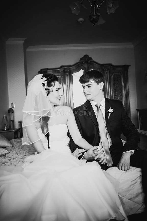 黑白色摄影美好的年轻夫妇坐床 免版税库存照片