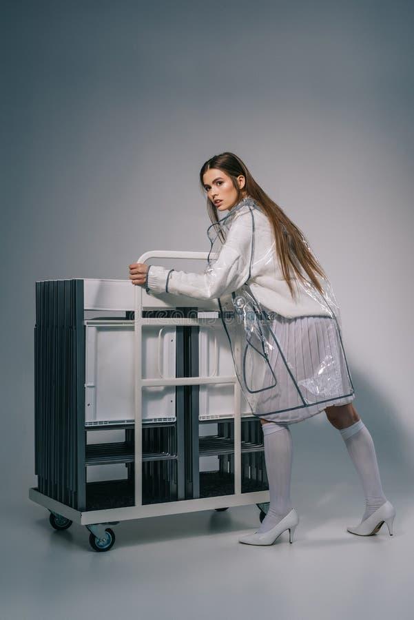 白色摆在与可折叠椅子的衣物和雨衣的时髦的女人后边在灰色 免版税图库摄影