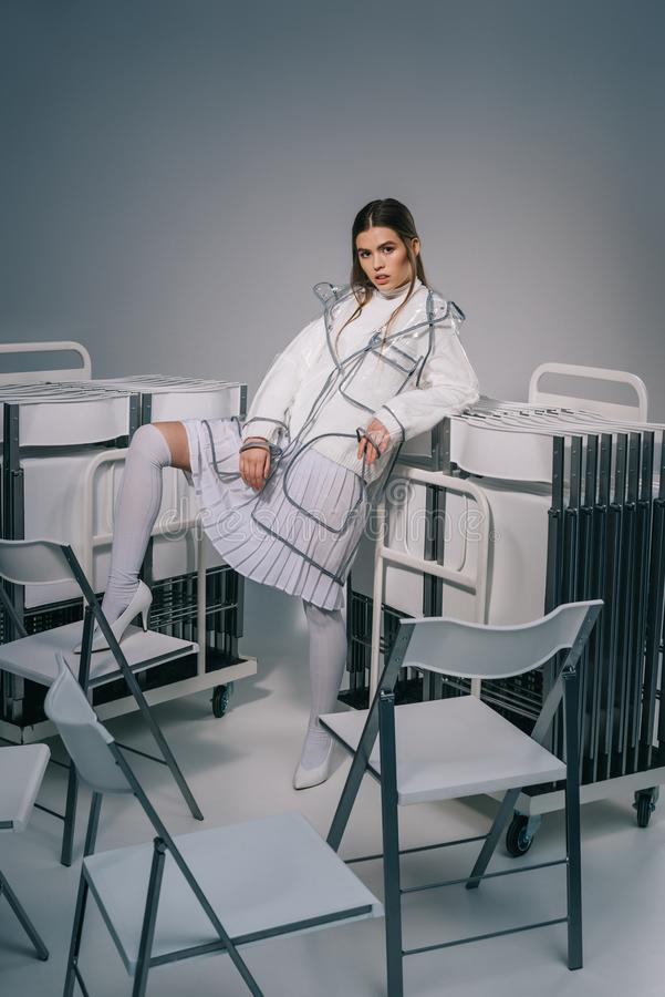 白色摆在与可折叠椅子的衣物和雨衣的时髦的女人后边在灰色 免版税库存图片