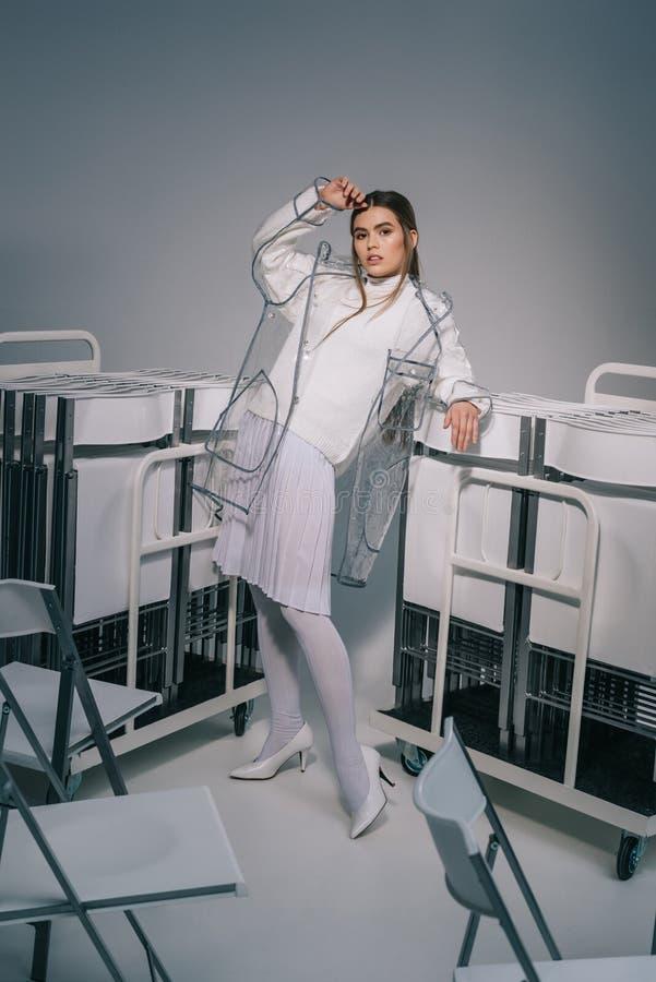 白色摆在与可折叠椅子的衣物和雨衣的时髦的妇女后边在灰色 免版税库存图片