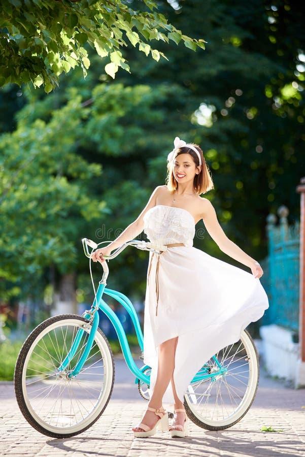 白色摆在蓝色自行车附近的礼服和高跟鞋的微笑的女孩在公园 免版税库存图片