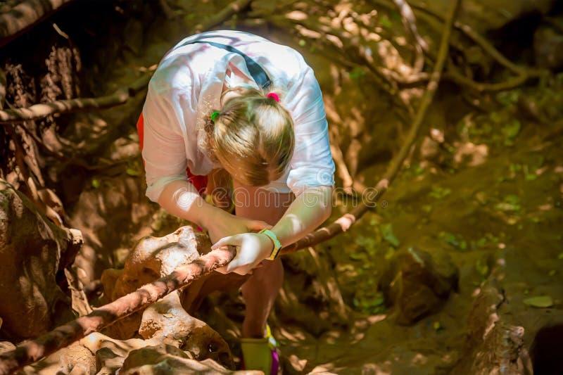 白色攀登的年轻女人在绳索的山 o 热带密林 看下来 免版税库存照片