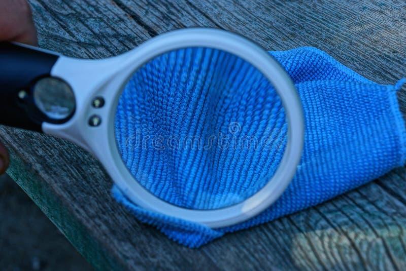 白色放大器在一张灰色木桌上增加在一蓝色餐巾microfiber的织品说谎 库存图片