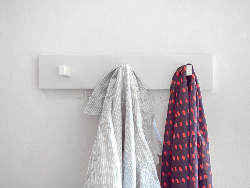 白色放松了镶边衬衣和红色圆点垂悬在白色墙壁上的白色挂衣架的样式围巾 免版税库存图片
