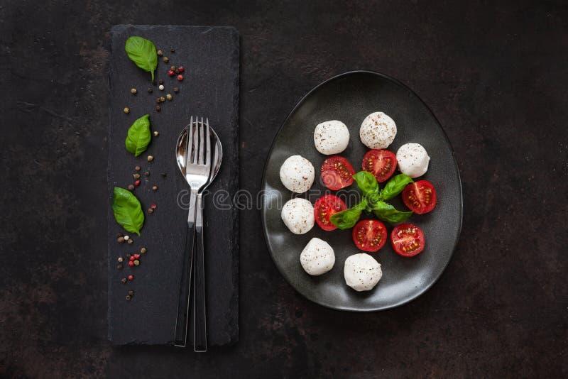 白色无盐干酪球乳酪、红色西红柿、橄榄油和蓬蒿特写镜头在黑暗的具体背景 顶视图,平的位置 免版税库存图片