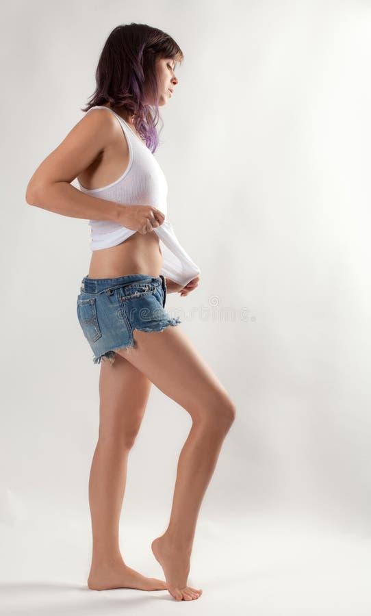 白色无袖衫和吉恩短裤的妇女 免版税库存照片
