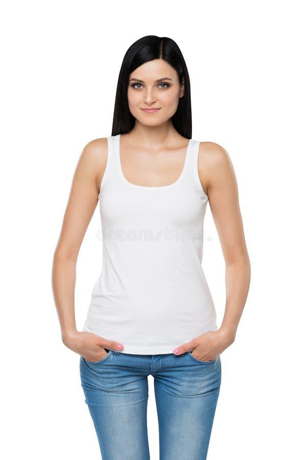 白色无袖衫和牛仔布的一名深色的妇女 手在口袋 图库摄影