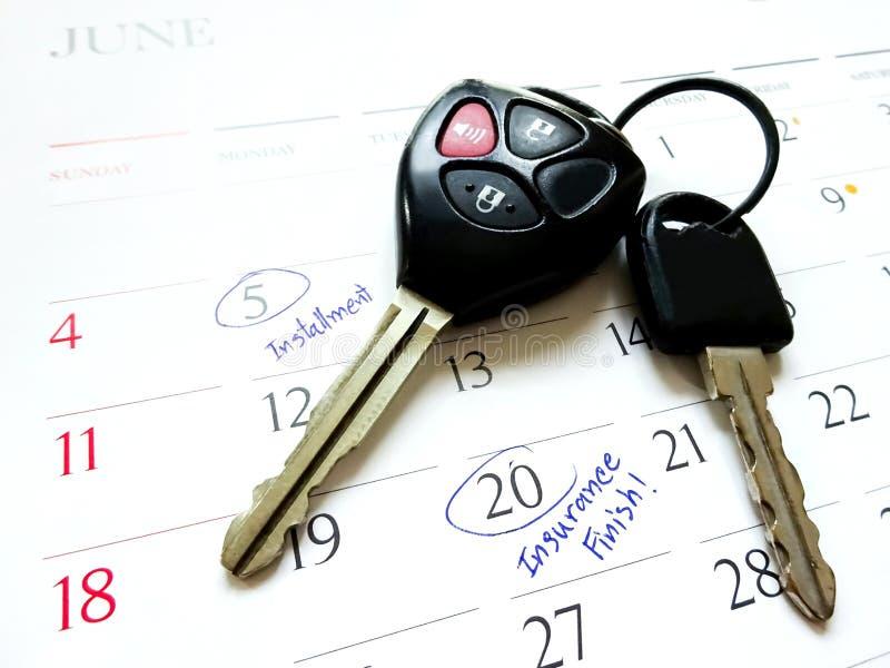 白色日历上的车钥匙,在日期号上标记圆 免版税库存图片