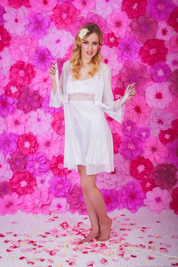 白色晨衣的白肤金发的美丽的妇女 库存图片