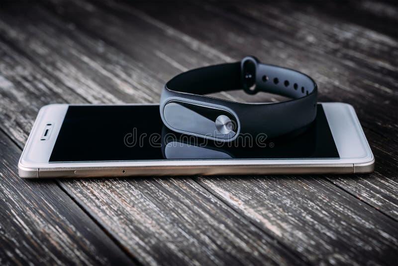 白色智能手机的黑人健身跟踪仪在木桌上 库存照片