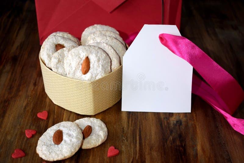 白色曲奇饼用在一个心形的箱子的杏仁 文本的空插件 免版税库存照片