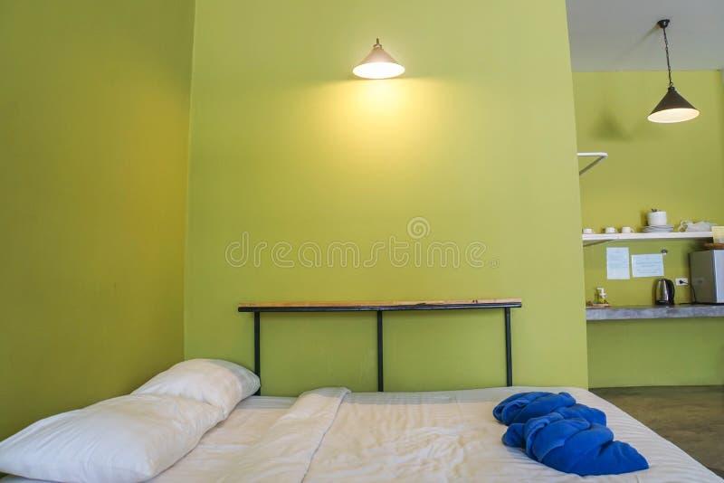 白色最小的床在有绿色墙壁的卧室 图库摄影