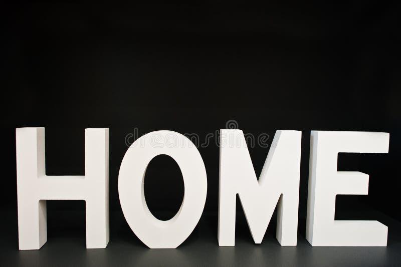 白色木信件回家在黑背景 库存照片