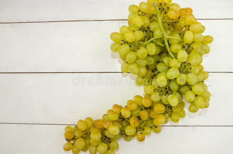 白色木桌上的绿色葡萄 从上方查看 大地葡萄 库存照片