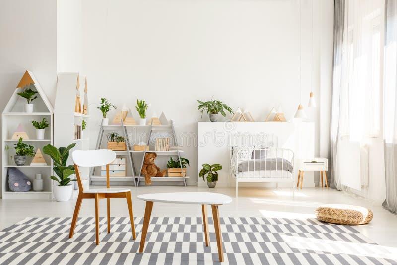 白色木椅子和桌集合,宽敞,被日光照射了少年卧室内部的绿色植物与斯堪的纳维亚装饰 免版税库存照片