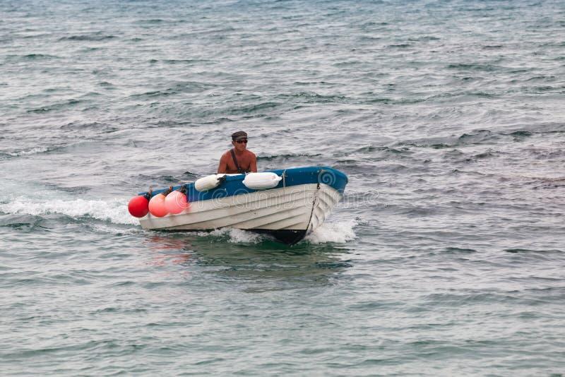 白色木汽船的渔夫 免版税库存照片