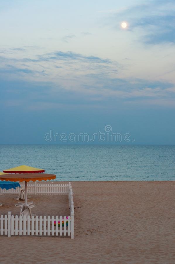 白色木篱芭正方形在海滩沙子的有暗淡的夏天海景背景 免版税库存照片