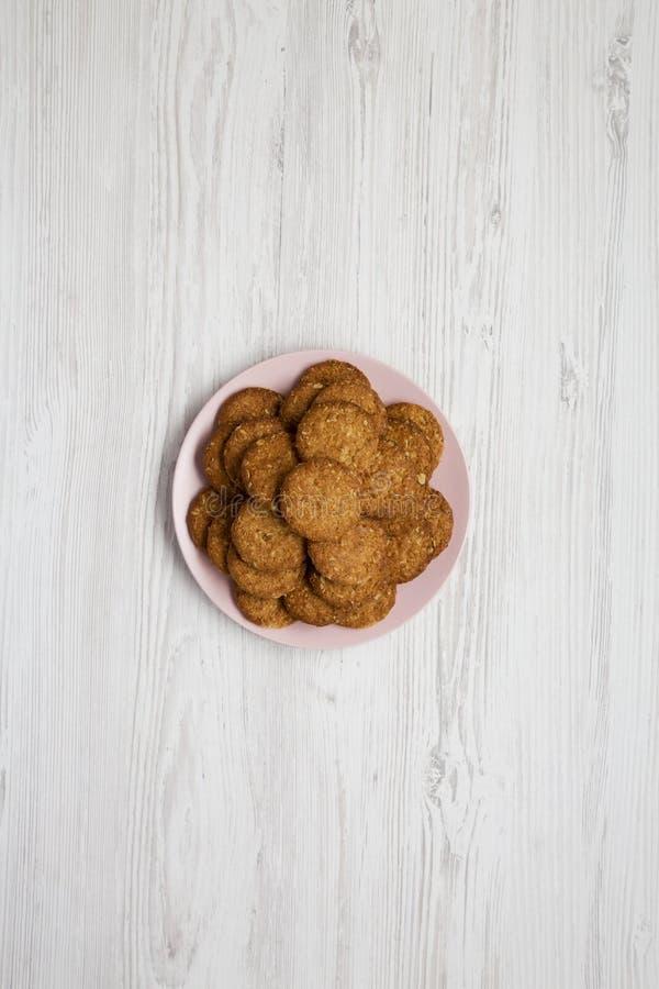 白色木色背景中粉红的盘子上的谷类饼干,顶视图 平躺,头顶,从上面 库存照片