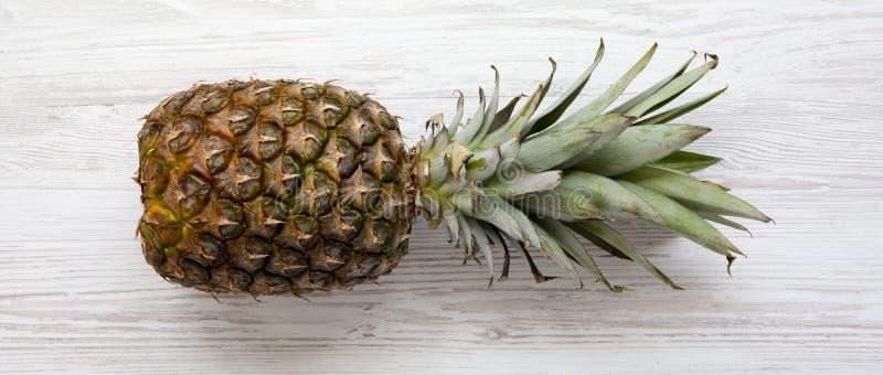 白色木表面上的大成熟菠萝,顶视图 从上,顶上 免版税库存图片