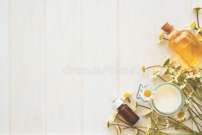 白色木质背景下甘菊花和精油和提取物的化妆品瓶 平躺 顶视图 复制空间 库存照片