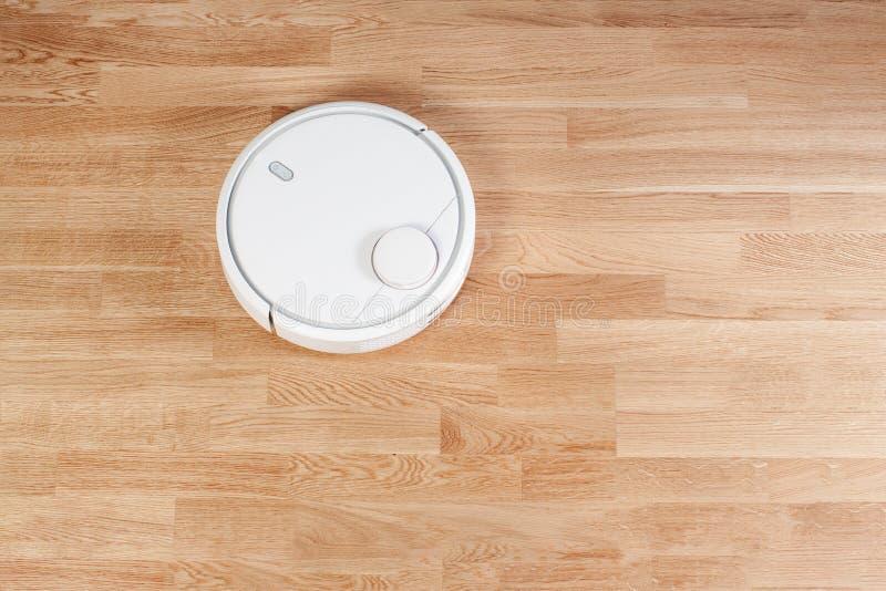 白色机器人吸尘器在层压制品的地板上跑 现代聪明的清洁工艺家务 平的位置顶视图 您 免版税库存图片