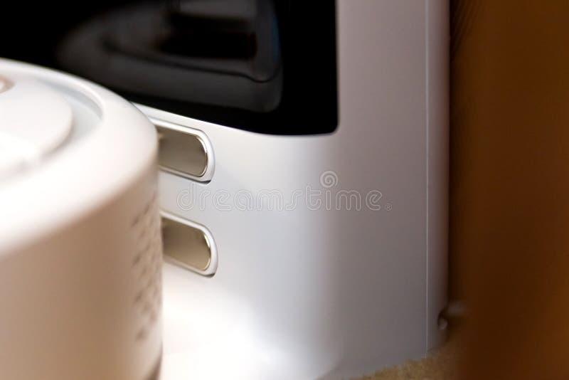 白色机器人吸尘器的充电站联络充电在基地的 现代聪明的电子家务技术 库存照片