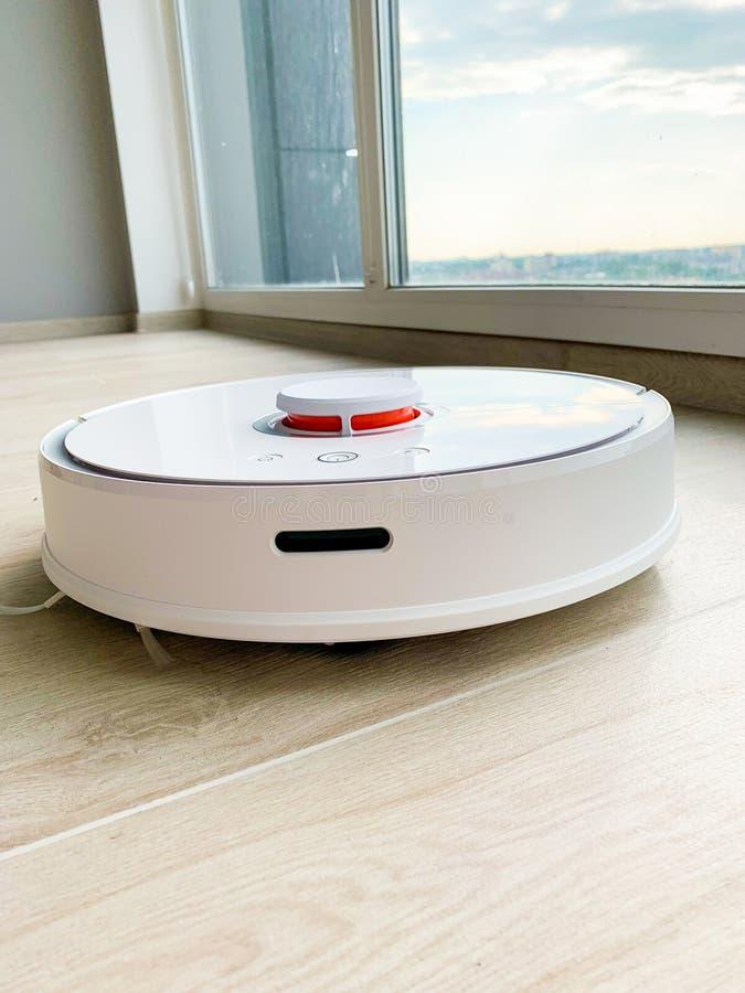 白色机器人擦净剂 机器人在层压制品的地板上的吸尘器在行动 免版税库存照片