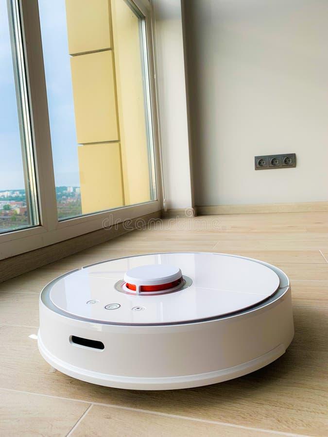 白色机器人擦净剂 机器人在层压制品的地板上的吸尘器在行动 免版税图库摄影