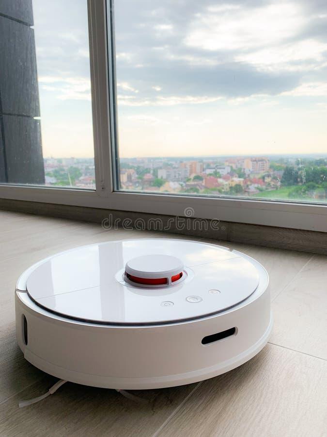 白色机器人擦净剂 机器人在层压制品的地板上的吸尘器在行动 库存图片