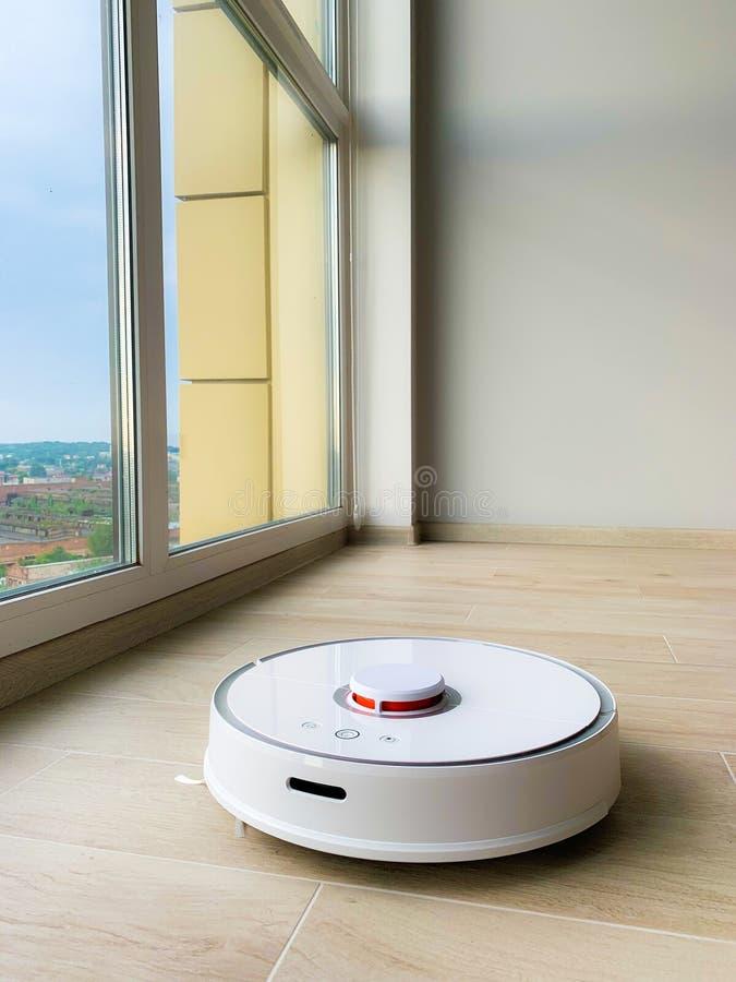 白色机器人擦净剂 机器人在层压制品的地板上的吸尘器在行动 图库摄影