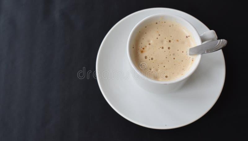 白色杯在黑背景的热奶咖啡 免版税库存照片