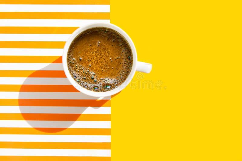 白色杯子与泡沫似的crema的新近地煮的咖啡在duotone黄色白色镶边背景 r 早晨早餐能量 库存照片
