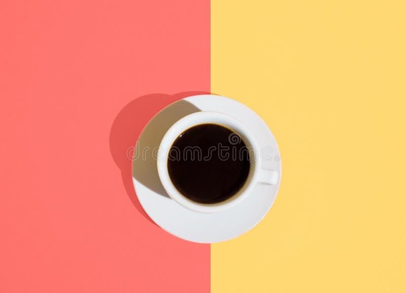 白色杯子与茶碟的新近地煮的咖啡在时髦duotone居住的珊瑚淡色沙子颜色背景 早晨能量 免版税库存照片