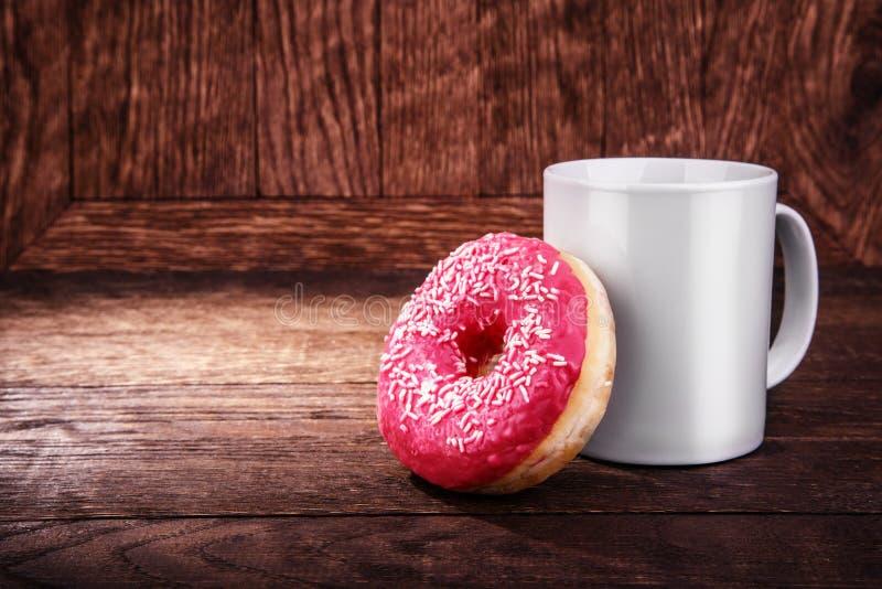 白色杯子和一个多福饼在木 免版税图库摄影