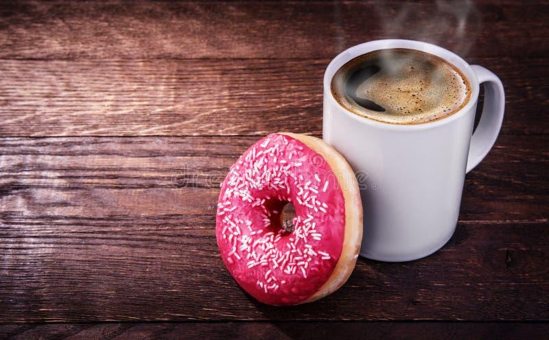 白色杯子咖啡和一个多福饼在木背景 图库摄影