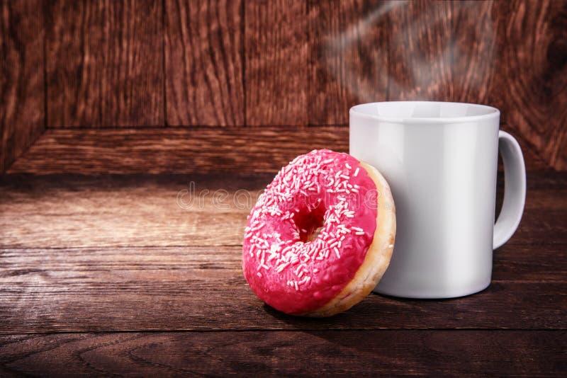 白色杯子咖啡和一个多福饼在木背景 库存照片