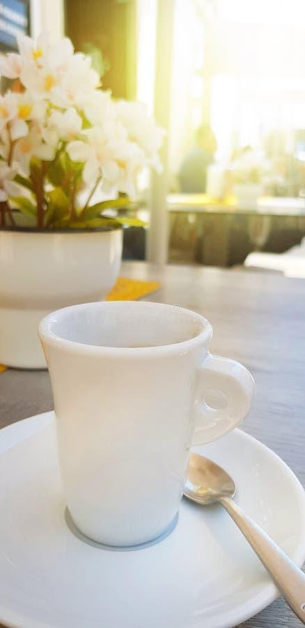 白色杯子在一张桌上的新鲜的浓咖啡咖啡与花 E 免版税库存图片