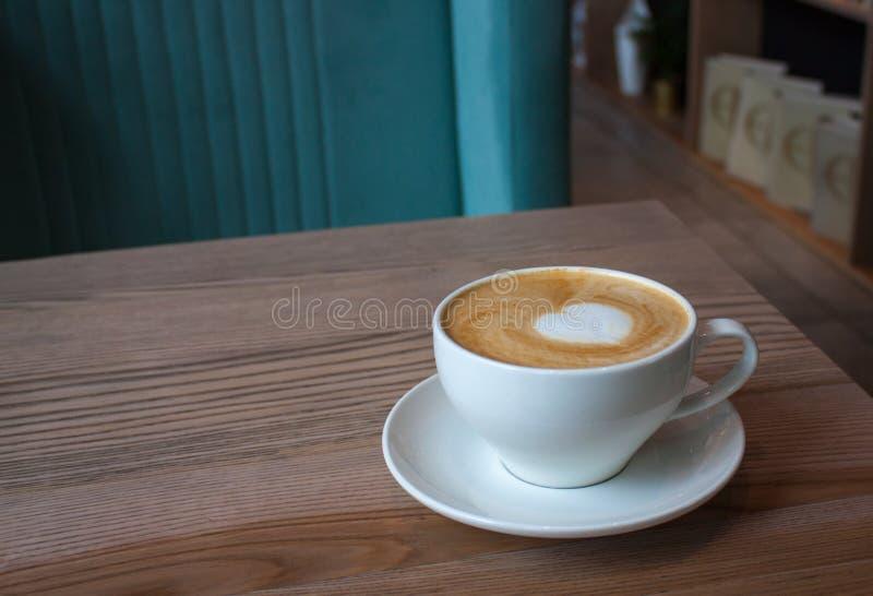 白色杯子在轻的木桌上的热奶咖啡 免版税库存图片