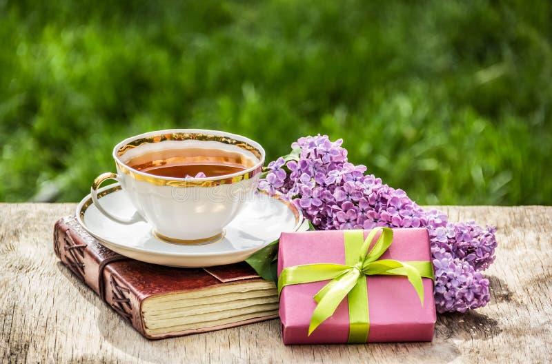白色杯子用茶、花和礼物盒 茶和丁香在一张老木桌上分支 免版税库存图片