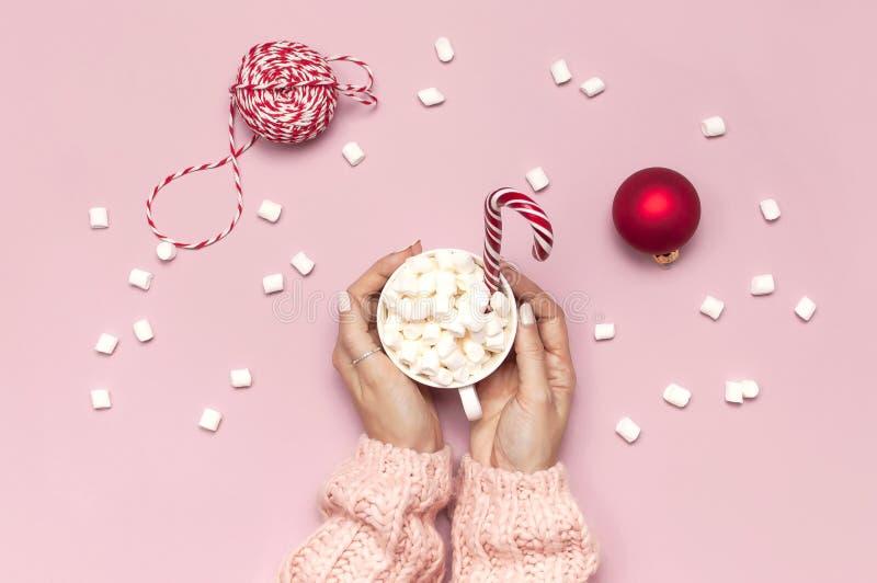 白色杯子用蛋白软糖在女性手上在桃红色背景顶视图的被编织的毛线衣棒棒糖礼物盒红色球 库存图片