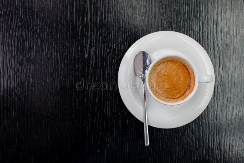 白色杯热奶咖啡或expresso咖啡与泡沫在桌上在一个咖啡馆与匙子 库存图片