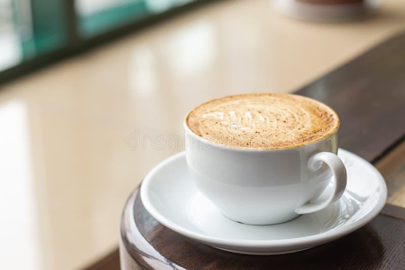 白色杯热奶咖啡用桂香和完善的crema 在木桌上的咖啡在咖啡馆窗口旁边 库存照片