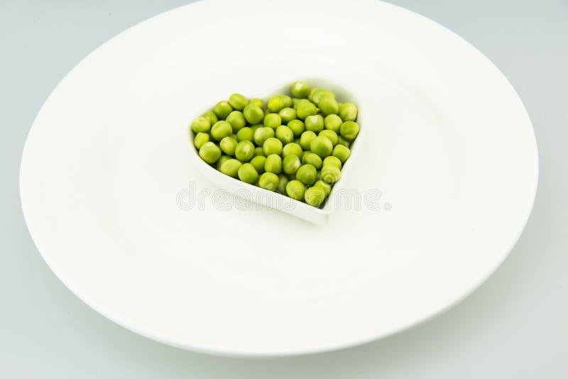 白色板材,一块心形的小,新鲜的豌豆板材 免版税库存图片
