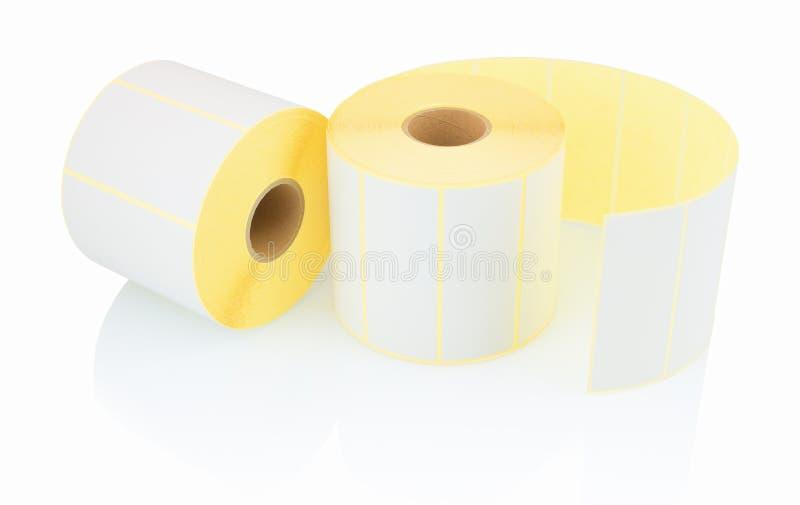 白色标签在与阴影反射的白色背景滚动 标签白色卷轴打印机的 免版税库存照片