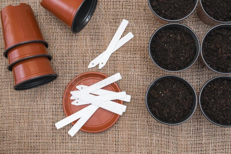 白色标记和棕色罐有土壤的在麻袋布背景 免版税图库摄影
