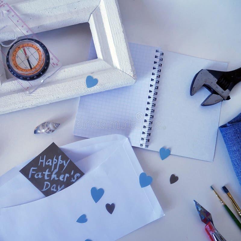 白色框架、一个指南针、壳在轻的背景和一张明信片对父亲的天 免版税库存照片