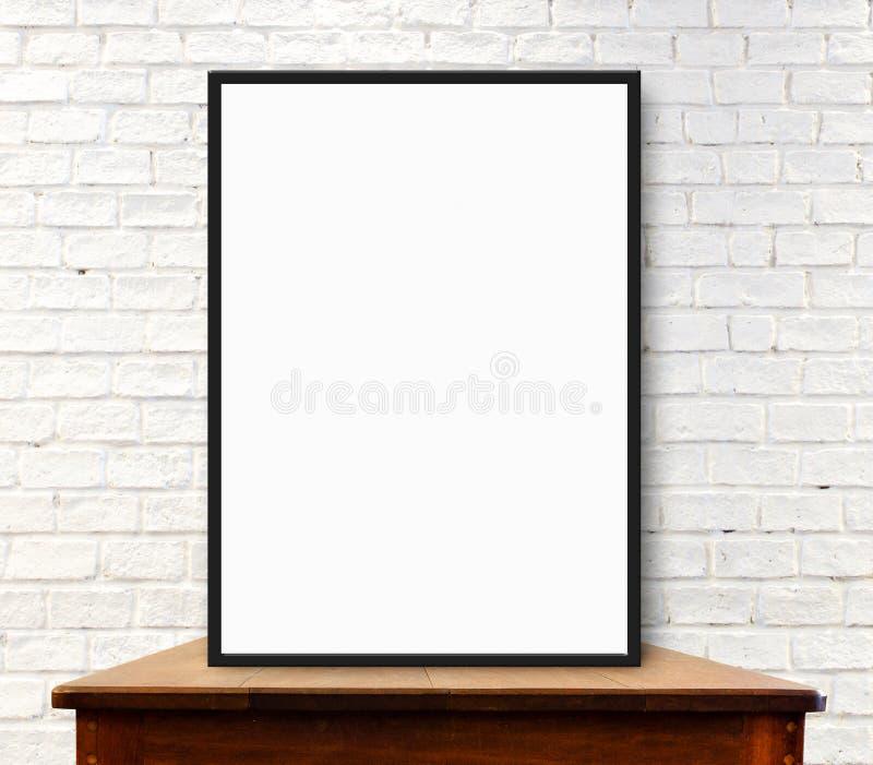 白色框架嘲笑在白色砖墙的木桌上 库存图片