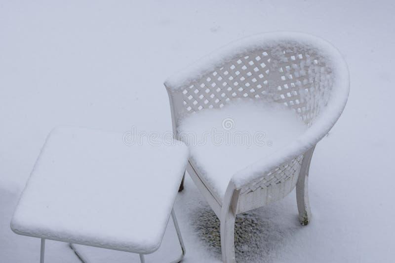 白色桌和在雪厚实的层数盖的躺椅在冬天季节,庭院休息室集合期间在冬天 库存图片