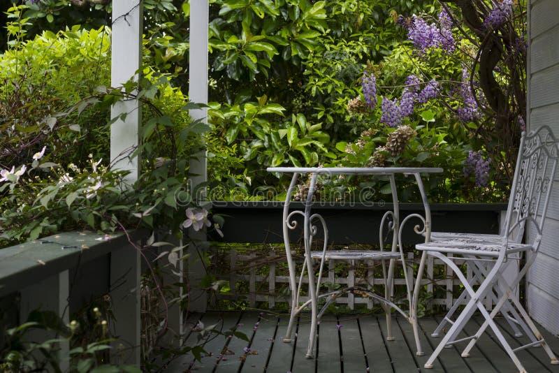 白色桌和椅子在门廊和树与紫色花 免版税库存照片